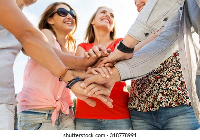 success, people, teamwork and gesture concept - close up of happy  friends  with hands on top of each other outdoors