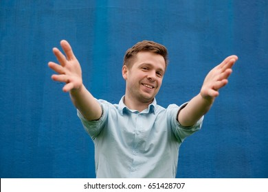 Success positive emotions. Happy young man in blue shirt stretching hands ahead, wanting to hug someone