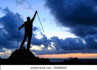 Success silhouette backpacker accomplish on top, man looking at inspirational ocean and island, camping in mountains on mountain peak. Motivation for fitness and healthy lifestyle outdoors in nature.