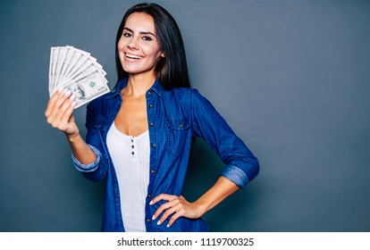 Success start up. Smiling young woman holds a lot of dollars in her hand and looks in camera. Winning the lottery or stock
