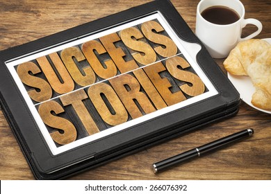 success stories typography - word abstract in vintage letterpress wood type on a digital tablet with a cup of coffee
