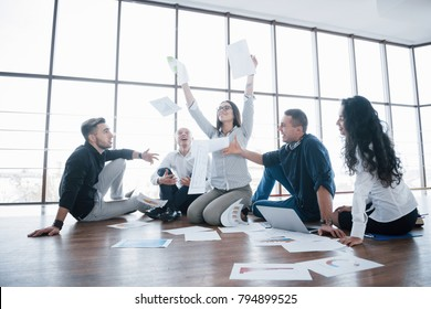 Success strategy together. Cheerful business colleagues tossing papers at creative office. Cooperation corporate achievement and teamwork concept.