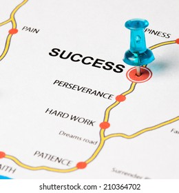 Success as target in the dreams road. Conceptual image where the cities are the principles that lead to the success target. Selective focus on the thumbtack.