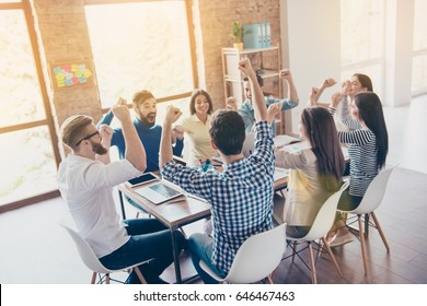 Success and team work concept. Team of business partners with raised up hands in light modern workstation, celebrating the breakthrough in their company