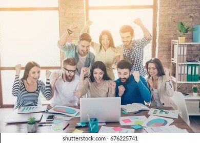 Success and team work concept. Group of business partners with raised up hands in light modern workstation, celebrating the breakthrough in their company