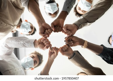 Success And Teamwork Concept. Below view of young diverse group of business people in protective medical masks making fist bump standing in circle. Workers do fist pump together celebrating good deal