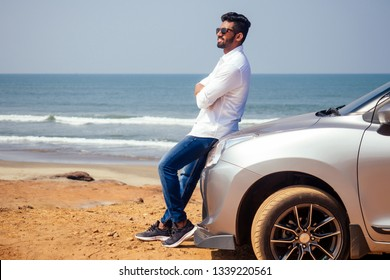 success traveler driver indian model male in a white shirt freelancer smiling and posing seacost .Handsome bearded man is standing near car freelancing on the beach
