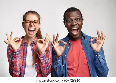 Success, triumph and victory concept. Mixed race couple of European girl and African American guy showig ok sign with fingers, their looks expressing excitement, amazement, joy and happiness