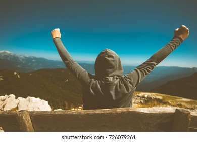Success, triumph and victory. Victorious female person standing on mountain top with arms raised in V. Achievement and accomplishment in life. Toned image.
