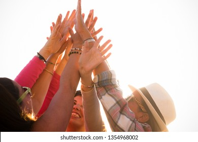 Success victory and teamwork concept with group of young nice women friends giving up hands together to the sky on a white clear background - Happiness and friendship for team people concept