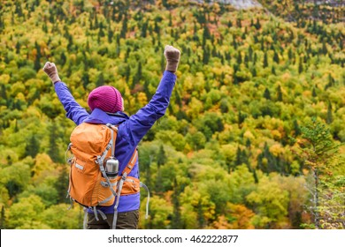 Success winner woman hiker cheering of happiness and joy on mountain in autumn nature. Hiking person happy of life goal achievement arms up raised to the sky as winning gesture.