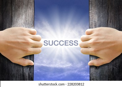 Success word floating and shining in the sky while two hands opening an old wooden door.