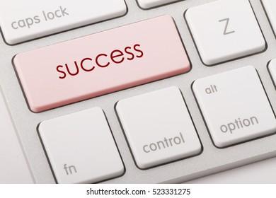 Success word written on computer keyboard.