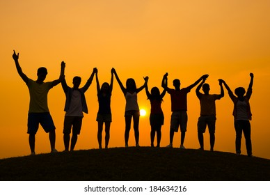 Success: Young People Celebrating at Sunset