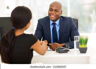 successful african american businessman handshaking with client in office