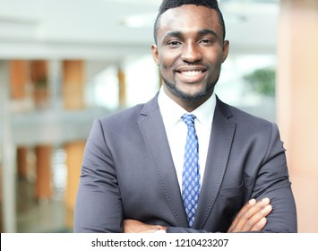 Successful African American businessman businessman standing in office.