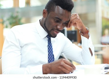 Successful African American businessman writing notes in paper, sitting at his spacious office.
