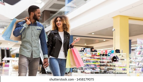 Successful african american couple spending time together after shopping in mall center, panorama, free space