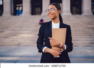 Successful African American graduate juridical specialist standing outdoors against courthouse building with folder in hands. Prosperous female student of high economic university in elegant wear