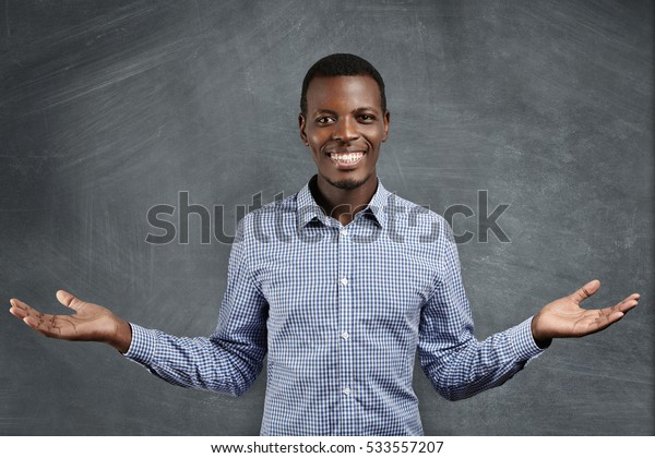 Successful African businessman with happy and confident smile dressed in blue checkered shirt holding his hands in welcoming gesture as if inviting you to work in his company, standing at blackboard