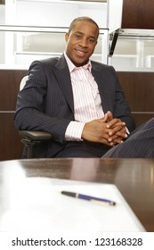 Successful African businessman relaxing in a chair in front of his desk at the office