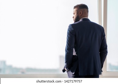 Successful african businessman in suit in office looking through window at city buildings, planning new projects, waiting for meeting, free space