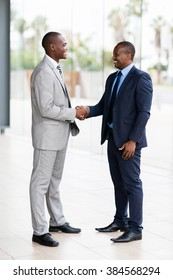 successful african businessmen handshaking in conference hall