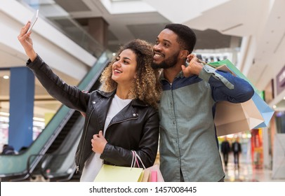 Successful african couple making selfie after shopping in mall center, blurred background