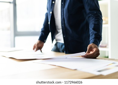 Successful African entrepreneur studying documents with attentive and concentrated look, drinking coffee. Dark-skinned businessman focused on work issues