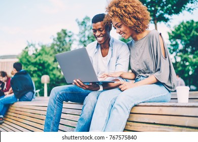 Successful afro american best friends dressed in casual clothing joking and laughing during using modern device sitting on bench.Happy man and woman watching funny video in website on laptop computer