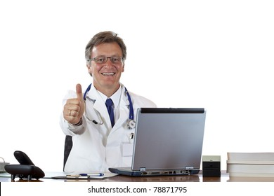 Successful aged doctor sitting at desk holds thumb up.Isolated on white background.