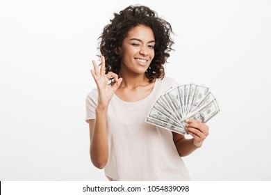Successful american woman with curly dark hair holding fan of money dollar bills and showing ok sign isolated over white background