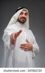 Successful arab businessman. Closeup low angle image with selective focus of Arab business man stretching out his hand while standing against grey background
