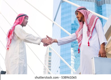Successful Arabic business people shaking hands on cityscape background