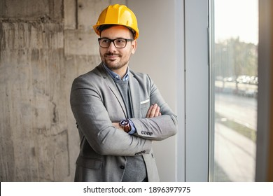 Successful architect standing in building in construction process with arms crossed and looking away.