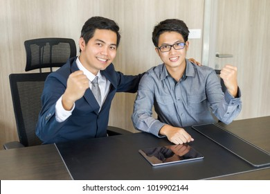 Successful asian business team of two sitting in office and planning work