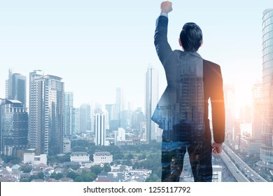 Successful asian businessman raised arm to the sky with cityscape background. Business concept. Double exposure