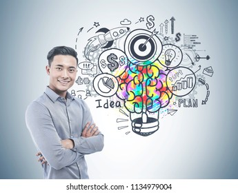 Successful Asian businessman smiling and standings with crossed arms near a gray wall with a creative business start up idea sketch