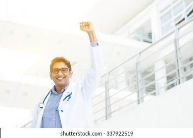Successful Asian Indian medical doctor with arm up celebrating his victory, hospital building as background.