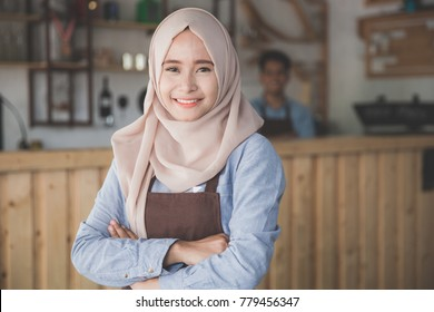 Successful asian muslim woman coffee shop owner standing with crossed arms