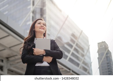 Successful asian senior businesswoman holidng digital tablet standing and looking over modern office background, startup and business concept