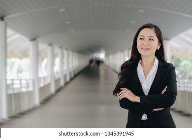 Successful asian senior businesswoman leader standing over modern pathway background