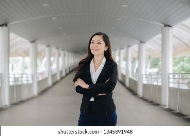 Successful asian senior businesswoman leader standing over modern pathway background
