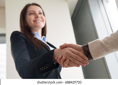 Successful attractive business lady shaking male hand and smiling, welcoming partner or client, starting finishing negotiations, establishing partnership, closing deal, focus on handshake