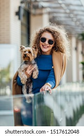 Successful attractive woman wearing at nude coat looking at camera and holding Yorkshire terrier. Yorkshire terrier concept. Fashion woman concept.