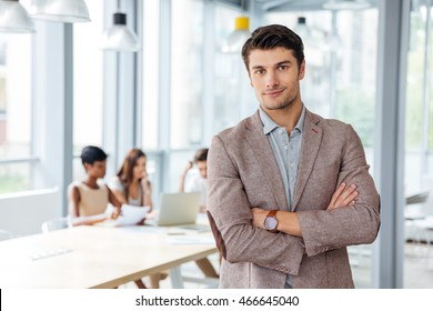 Successful attractive young businessman standing with arms crossed in office