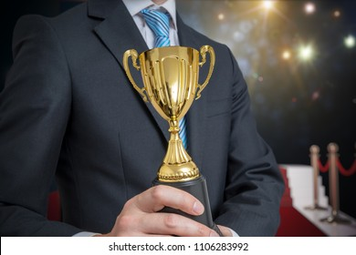 Successful awarded businessman is holding golden trophy. Lights and flashes in background.