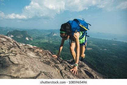 successful backpacking woman running up to the mountain top on cliff edge