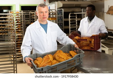 Successful baker during daily work in bakeshop. High quality photo