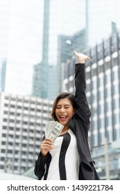 Successful beautiful Asian business  woman holding money US dollar bills in hand , business concept